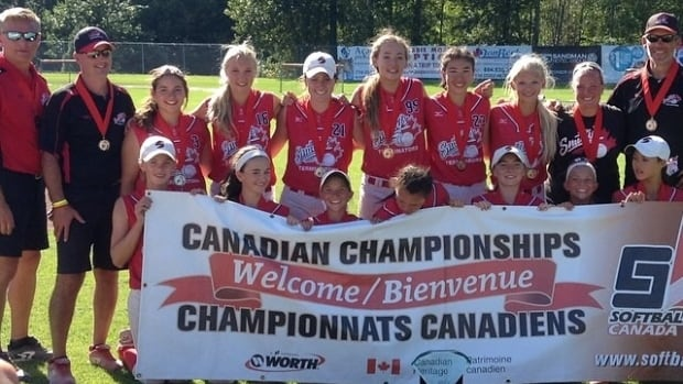 A group of 13 and 14-year-old softball players from Manitoba hold up a banner after winning gold in a national championship for the first time ever.