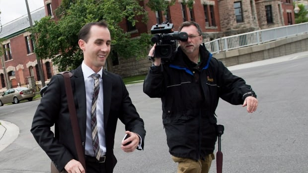 Former Conservative party staffer Michael Sona runs past a news videographer while leaving court in Guelph, Ont. on Thursday.