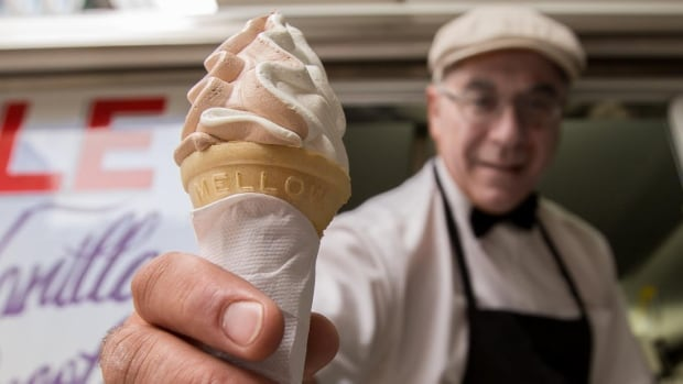 Ake Alexopoulos hands out a soft-serve ice cream cone from the side of his ice-cream truck in downtown Toronto. The city has more than 130 licensed trucks.