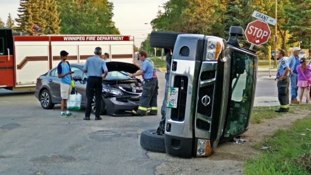A truck sits on its side after a crash at Grant Avenue and Elmhurst Road in Winnipeg Thursday night.