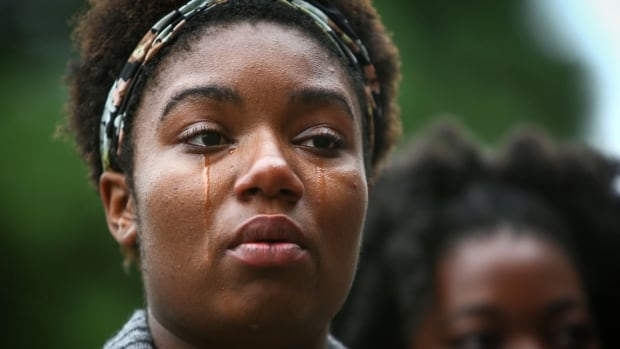 Zenobia Taylor, 17, becomes emotional during a National Moment of Silence gathering Thursday, Aug. 14, 2014, in Seattle. People in more than 90 cities observed Thursday's National Moment of Silence.