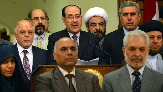 Iraq's prime minister for the past eight years, Nouri al-Maliki, is surrounded by Iraqi lawmakers as he announces that he is stepping down.