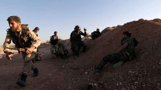 Free Syrian Army fighters are seen together in Wadi Al-Dayf in the southern Idlib countryside July 16, 2014. The rebel group is asking the U.S. to conduct air strikes on Islamic State fighters near the northern city of Aleppo.