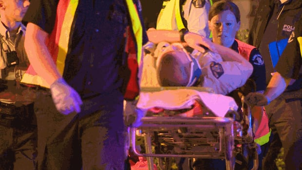 A Surrey RCMP officer is loaded onto an ambulance after being freed from the car in which he was trapped.