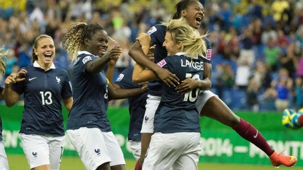 France's Claire Lavogez is mobbed by teammates after scoring the winning penalty against South Korea during their quarter-final at the FIFA U-20 women's World Cup  in Montreal on Sunday.