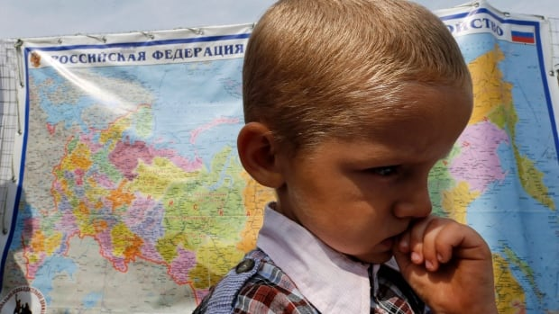 A boy stands in front of a map of Russia at a temporary tent camp set up for Ukrainian refugees outside Donetsk. Ukraine troops and rebels accused each other of attacking a refugee convoy.