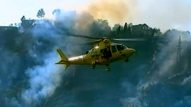 In this frame grab from a footage by Rainews 24, a rescue helicopter overflies the flames burning the bush after two Italian air force fighter jets carrying a total of four crew members collided during a training mission on Tuesday.