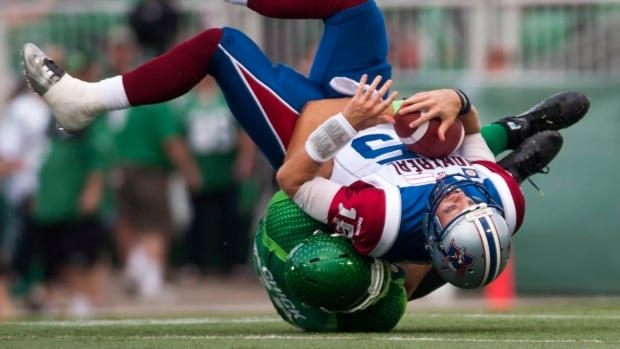 Montreal Alouettes quarterback Alex Brink is sacked by Saskatchewan Roughriders defensive end John Chick during the third quarter of CFL football action on Saturday, August 16, 2014 in Regina.