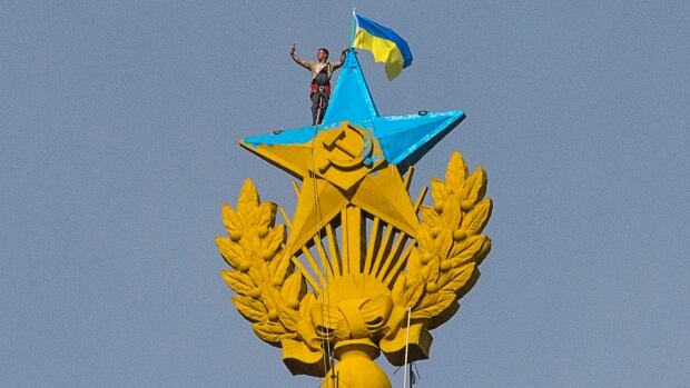 A man takes a selfie Wednesday as he stands with a Ukrainian flag on a Soviet-style star re-touched with blue paint so it resembles the yellow-and-blue national colours of Ukraine, atop the spire of a building in Moscow.