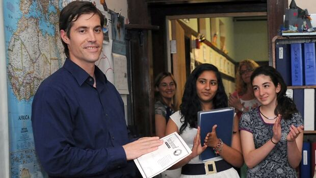 Journalist James Foley receives applause from students at a school in Framingham, Mass., in 2011. Interpol is particularly concerned that a man who appears in a video of journalist James Foley's death may be British.