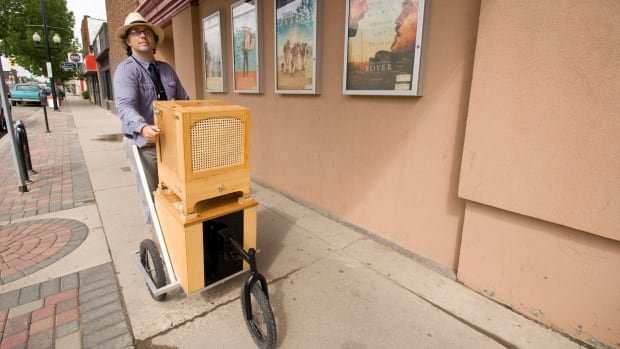 Mark Prier pushes his handmade busker organ through Saskatoon's Riversdale neighbourhood. The organ dispenses birdseed and is part of the city's Placemaker public art program.