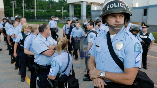 Police in riot gear prepare to take up positions on Aug. 16, 2014, as people protest the police shooting death of Michael Brown in Ferguson, Mo., on Aug. 9. Companies that make cameras for officers to wear are seeing much greater interest in their products in the wake of that shooting.
