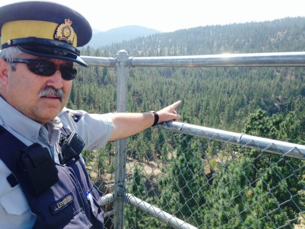 RCMP Const. Jacques Lefebvre points to Trout Creek canyon