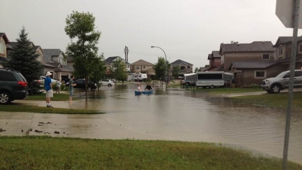 People in Winnipeg's Whyte Ridge neighbourhood canoed in the streets on Thursday. The area saw up to 81 millimetres of rain that evening.
