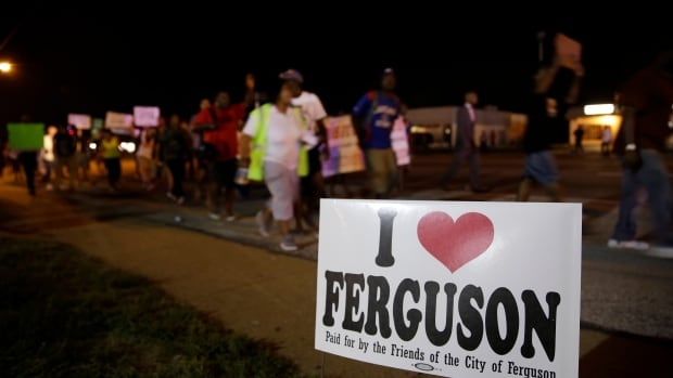 Protesters march Thursday night in Ferguson, Mo. The city's streets were peaceful, as the protests eased and the National Guard was ordered to withdraw.