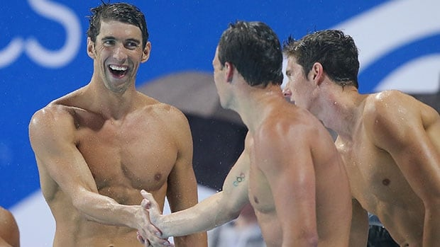 Michael Phelps, left, celebrates with teammates Ryan Lochte, centre, and Conor Dwyer after their 4x200m relay victory in Gold Coast, Australia.