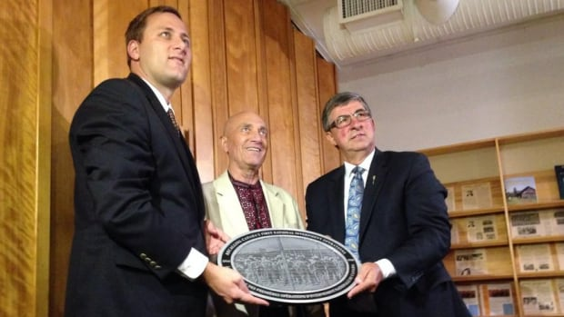 MP Brad Trost (left),  Slawko Kindrachuk,  UCC-SPC president, and MLA Ken Krawetz hold a plaque commemorating the 100th anniversary of the War Measures Act being enacted at the St. Petro Mohyla Institute.