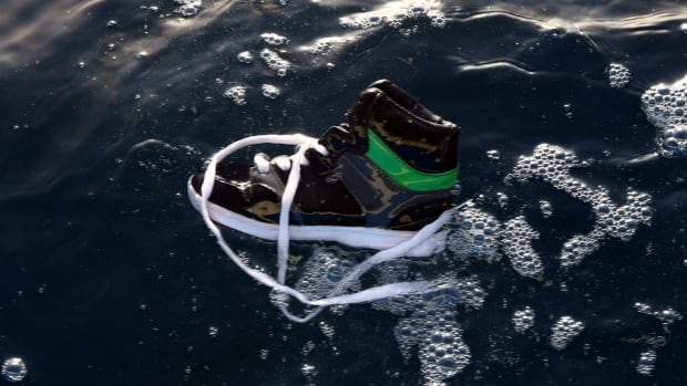 A shoe belonging to an African migrant floats in the waters near al-Qarbole, where the migrant ship sank.