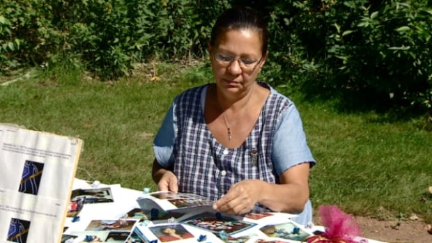 Peacha Atkinson looks over photos of her murdered daughter in Hawrelak Park on Saturday, Aug. 23, 2014. Atkinson said she was not surprised by Prime Minister Stephen Harper's dismissal of calls for a national inquiry into missing and murdered aboriginal women and girls.