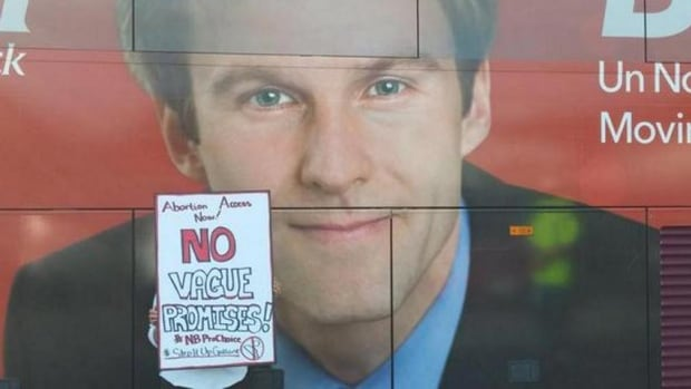 An abortion-rights activist holds up a sign in front of Liberal Leader Brian Gallant's campaign bus in Fredericton last week.