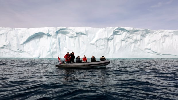 Then Prime Minister Stephen Harper, second right, rides in a Zodiac in front of a large iceberg on Eclipse Sound, near the arctic community of Pond Inlet, Nunavut, in 2014. A memo obtained by CBC shows the department's attempts to buy new inflatables have stalled.
