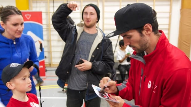 Speed skater and Olympic gold medalist Charles Hamelin signs autographs in Iqaluit on Monday.