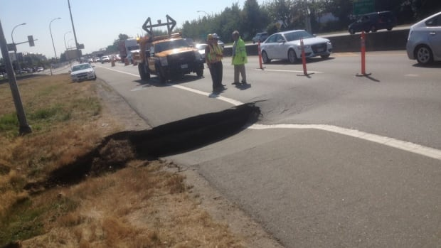Crews from the Transportation Ministry examine a sinkhole that appeared on Highway 99 in Richmond, B.C. Tuesday.