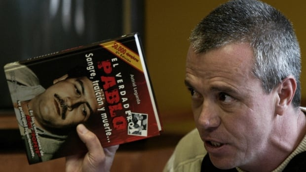 "John Jairo Velasquez, is seen giving testimony in 2006 while holding a book titled ""The True Pablo, Blood, Treason, and Death,"" during the trial against Alberto Santofimio Botero in Bogota."