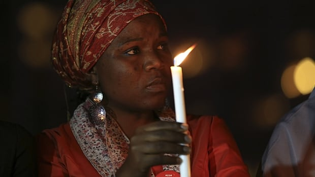 "A ""#Bring Back Our Girls"" campaigner takes part in a candlelight vigil in tribute for Dr. Ameyo Adadevoh, an endocrinologist who died after contracting Ebola, and other Ebola victims in Abuja yesterday."