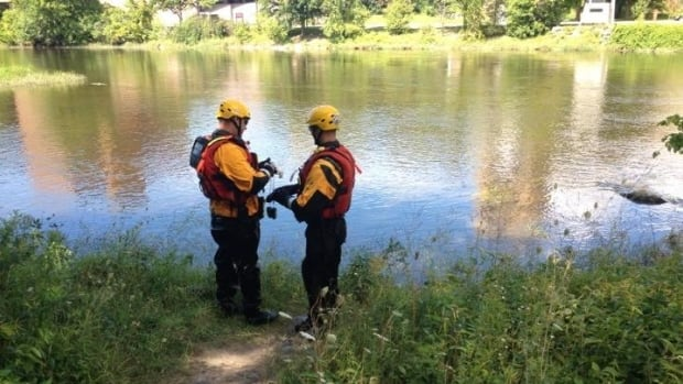 Ottawa police officers search the Rideau River Wednesday as part of their investigation into the discovery of a woman's body.