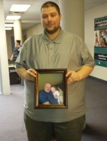 Burnett's son Andrew holds a picture of his father during Kyla MacLellan's sentencing hearing. (Moll