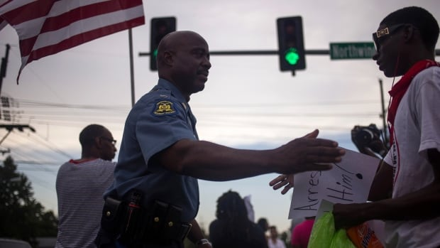 Captain Ron Johnson of the Missouri State Highway Patrol greets residents who were marching through Ferguson, Mo. on Tuesday.
