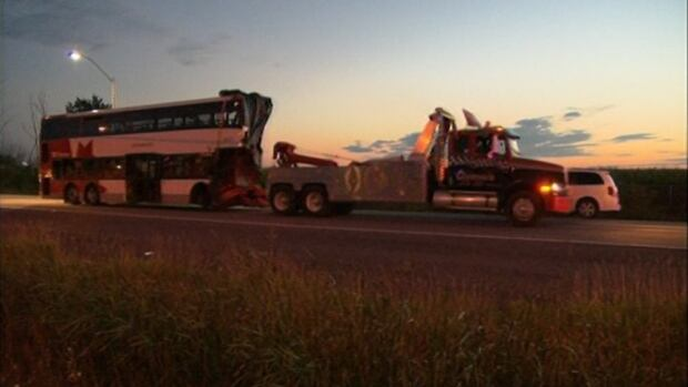 A tow truck moves the Ottawa transit bus from the scene of a fatal crash with a Via train Thursday, Sept. 19, 2013. The bus's route, number 76, will be retired as of Saturday.
