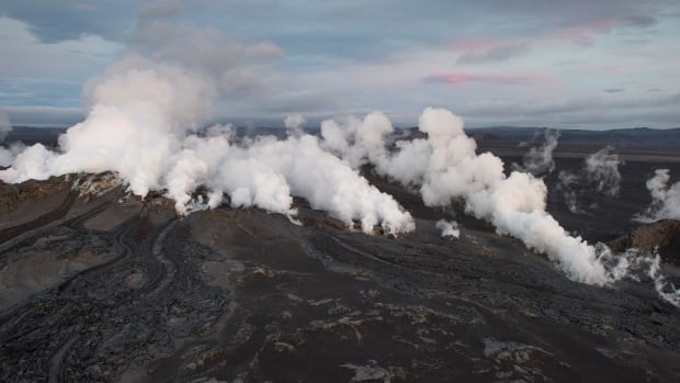 Steam and smoke rise over a one-km-long fissure in a lava field north of the Vatnajokull glacier, which covers part of Bardarbunga volcano system, on Friday. Iceland's Meteorological Office downgraded its volcano alert level to orange from red.