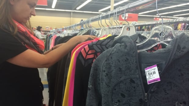 A Value Village employee sorts through sweaters at a store in Saskatoon, Sask. Winnipeg vintage store owner Kali Martin believes the for-profit store charges too much for used clothing and household items.