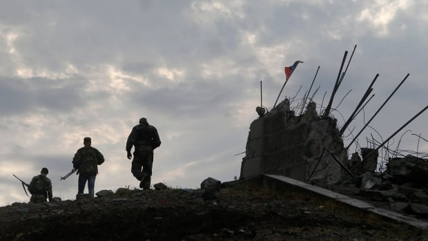 Pro-Russian separatists walk at a destroyed war memorial on Savur-Mohyla, a hill east of the city of Donetsk.