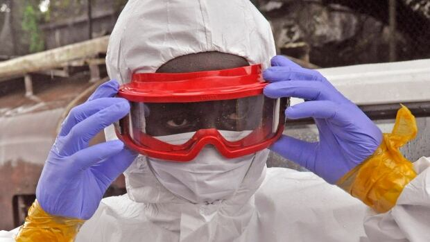 A Liberian health worker prepares to remove the body of a man that they believe died from the Ebola virus in Monrovia, Liberia, Friday. Meanwhile a Liberian health worker who recovered from the disease after receiving an experimental drug urges the manufacturer to speed up production and send it to Africa.