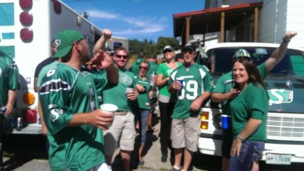 A group of Rider fans give the thumbs-down sign to the Winnipeg Blue Bombers as they tailgate outside of Mosaic Stadium in Regina ahead of the Labour Day Classic.