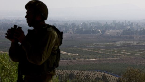 An Israeli soldier observes Syria's Quneitra province at an observation point on Mount Bental in the Israeli-controlled Golan Heights, overlooking the border with Syria. Fighting between Syrian troops and rebels focused around the town of Hamidiyeh in Quneitra province near the disputed frontier with Israel.