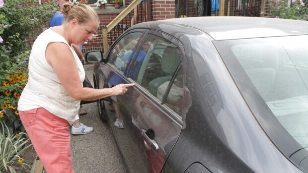 Lynda Spencer demonstrates paint damage to her car parked in front of her house on Balsam Avenue, across the street from the new Tim Hortons Field. She was told repainting could cost $2,900.