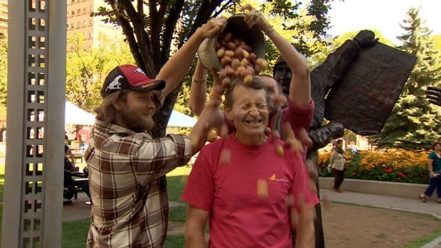 Alberta Liberal MLA David Swann gets doused with potatoes in an attempt to draw attention to the rights of farm workers in the province.