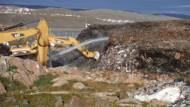 Crews spray water to begin dousing Iqaluit's three-month-long dump fire last August. Iqaluit deputy mayor Romeyn Stevenson says dealing with the city's waste is a pressing concern.