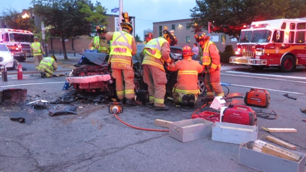 Firefighters work to free the driver of a car after a collision on Montreal Road Tuesday morning.