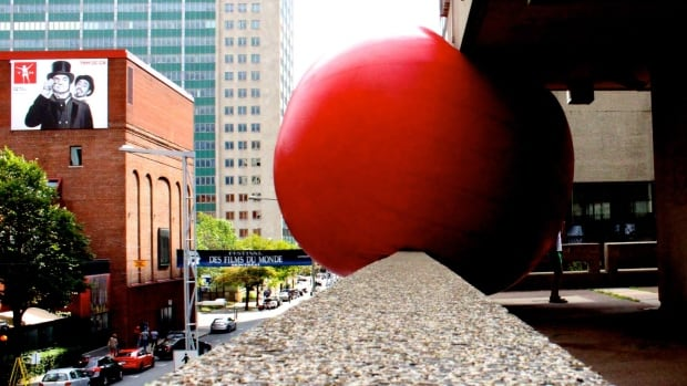 The RedBall perches on a ledge at Places des Arts.