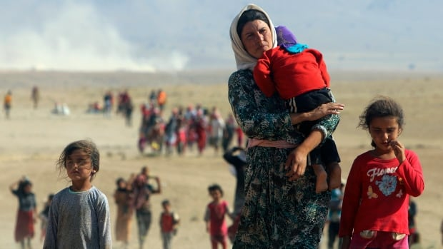 "Displaced people from the minority Yazidi sect fleeing toward the Syrian border in mid-August. Amnesty International says ISIS militants have abducted ""hundreds, if not thousands"" of Yazidi women and children."