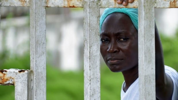 A medical worker at the John Fitzgerald Kennedy Hospital in Monrovia, Liberia, watches a demonstration during a strike for salaries and better security against the Ebola epidemic on Monday. The U.S. Centers for Disease Control says the outbreak needs more resources, expertise and a global, unified response.