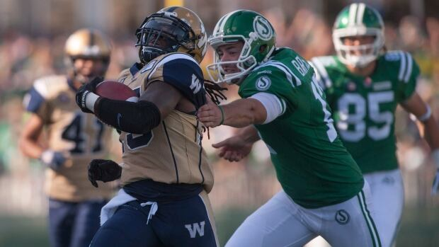 Winnipeg Blue Bombers defensive back Troy Stoudermire avoids a tackle from Saskatchewan Roughriders punter Josh Bartel during the fourth quarter of their Labour Day game in Regina on Aug, 31, 2014.