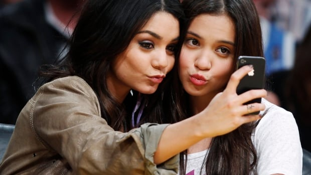 Actress Vanessa Hudgens, left, takes a photo with her sister Stella on her iPhone. Photos taken on an iPhone are automatically uploaded to the cloud for access on other devices when Apple's Photo Stream feature is activated.