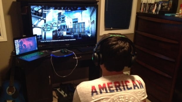 Spencer Clarke, 15, plays video games in his bedroom.