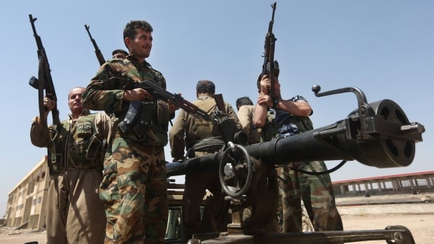 Kurdish Peshmerga fighters take positions on the front line against ISIS militants in a battle in June near Tuz Khormato, Iraq.